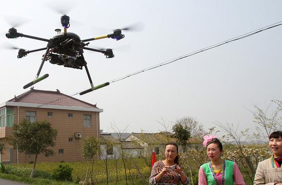 2014年4月8日,江苏南通几位参加活动的演员被正在航拍的无人机吸引。供图|视觉中国