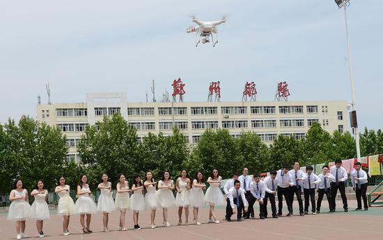 2016年5月22日,河南郑州,郑州航院的毕业生用无人机拍摄创意毕业照。供图|视觉中国