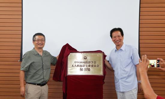 中国新闻摄影学会会长徐祖根(右)与光明网总裁杨谷为无人机专委会秘书处揭牌。(李运恒摄)