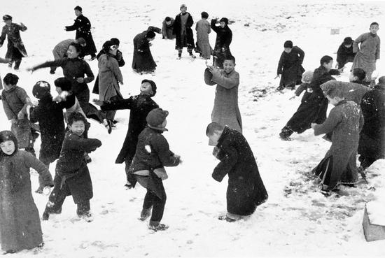 1938年3月,中国,汉口。一群孩子在雪地上打雪仗。© Robert Capa / International Center of Photograhy / Magnum Photos