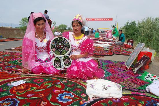 新疆生产建设兵第六师奇台农场的哈萨克族职工在展示她们的刺绣作品。