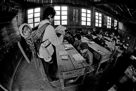 1987年4月,广西壮族自治区融水县安太乡寨怀村小学,戴红英老师把不满五个月的小女儿背着上课。