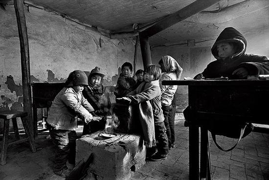 1991年12月,河北省滦平县拉海沟乡大店子村,烤烤冻僵的小手,再继续上课。