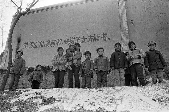 """1992年2月,甘肃省康乐县高集乡,村舍上到处可见这样的标语""""莫为近利误前程,快送子女去读书""""。"""