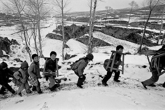 1992年3月,山西省静乐县赤泥洼乡羊丈村,扛着桌凳去上学。