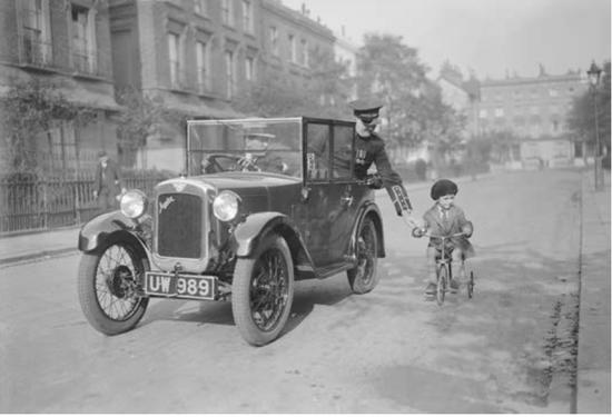 一名年轻的骑自行车的人从一辆奥斯汀七号汽车的乘客手中得到了一个帮助,High 先生在前往伦敦奥林匹亚汽车展的途进行普拉特运动精神测验。