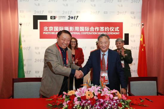 北京国际摄影周组委会执行主席杨元惺与巴西里约摄影节总协调人王卫光签约
