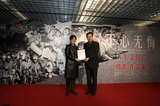 中国摄影家协会党组成员、秘书长高琴(左)为于文国颁发收藏证书