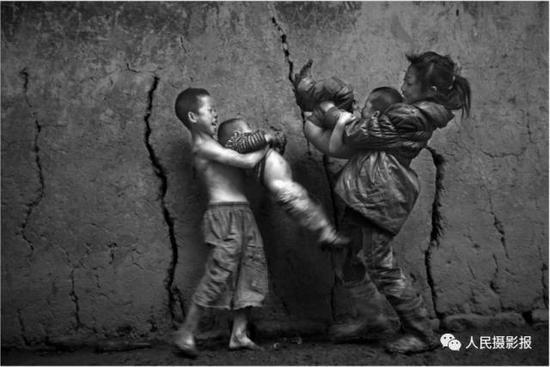 2014年8月11日,9岁的木衣抱着2岁的马格与和11岁的姐姐石地抱着4岁的马石正在玩耍。