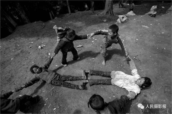 2014年6月7日,孩子们正在满地泥土的家门口玩耍。