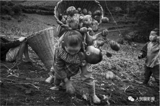 2015年7月23日,大一点的孩子常常胸前抱着弟弟妹妹,身后背着箩筐和柴火,这对孩子们早已习惯了。