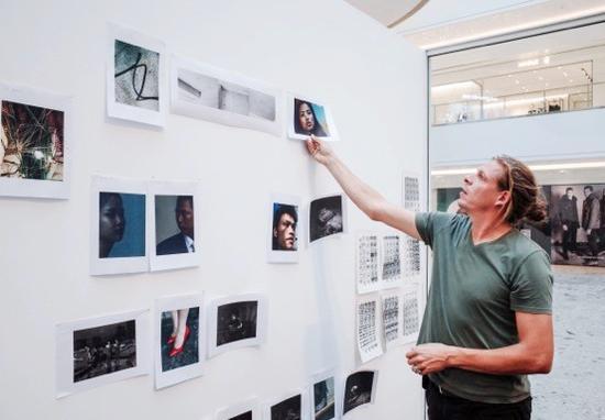 在Live Lab现场实验空间的一面白墙上,Alex Majoli正在编排作品。