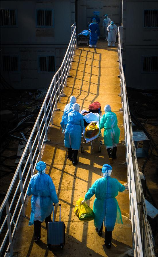 2月4日,醫護人員將新冠肺炎患者轉入僅僅10天就建成的武漢火神山醫院。肖藝九  見證?造像——抗擊疫情影像展覽參展作品