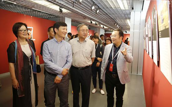 李舸(左二)、郑更生(右二)、高琴(左一)在高大鲲的陪同下参观手机单元入展作品。 张双双 摄