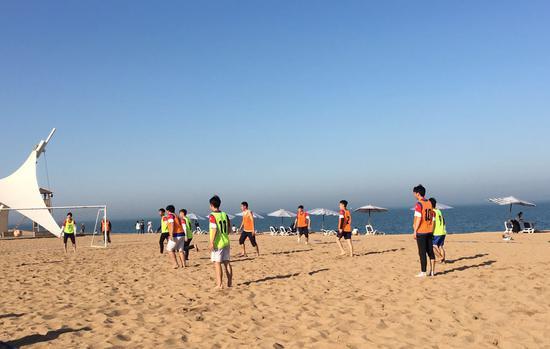 日照海边正在打球的市民。
