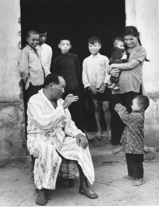 毛泽东畅游湘江后在农家门口与小孩逗趣。(1958年) 侯波 摄
