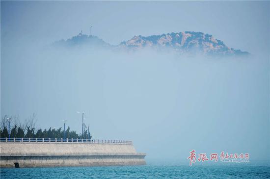 受春季温差影响,崂山区出现平流雾,远处崂山在海上时隐时现美如仙境。