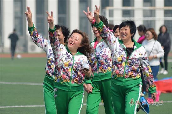 社区居民在趣味运动会上获胜,竖起V形手势庆贺。