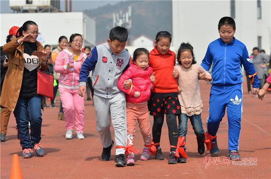 小朋友参加趣味运动会五人六足跑项目比赛。