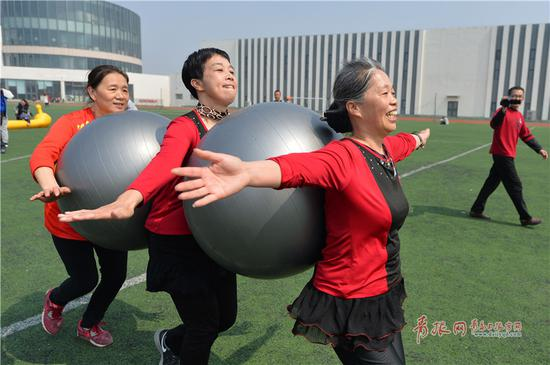 社区居民参加趣味运动会三人两球接力赛。
