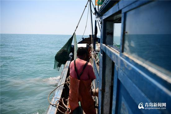 将装满鱼虾的渔网吊上甲板。