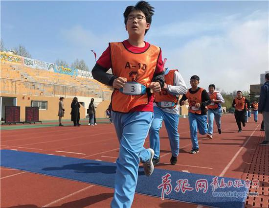 ▲考生腰系芯片感应腰带参加1000米考试,跑过蓝色感应垫。