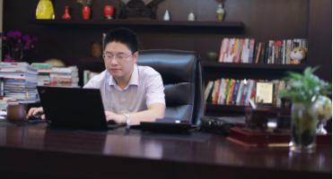 图为:胡玉建坐在办公室里工作