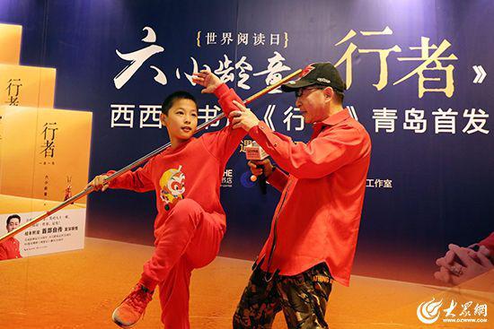 六小龄童现场与小粉丝切磋表演金箍棒。 大众网记者毕天宇摄