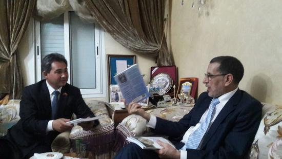 (摩洛哥首相萨阿德丁·奥斯曼尼向中华伊斯兰关系理事会主席丁厚飞博士赠送自己的医学著作。)