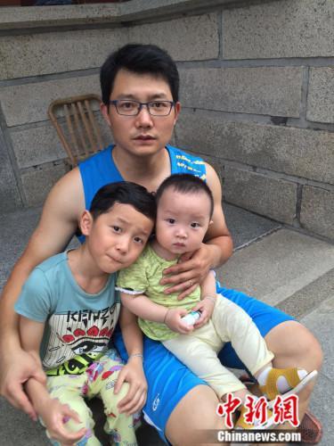 """图为二孩""""奶爸""""和两个可爱的孩子。吕春荣 摄"""
