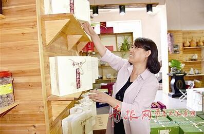 吕秀芹在自家的土特产店里摆放产品。 陆 波 摄