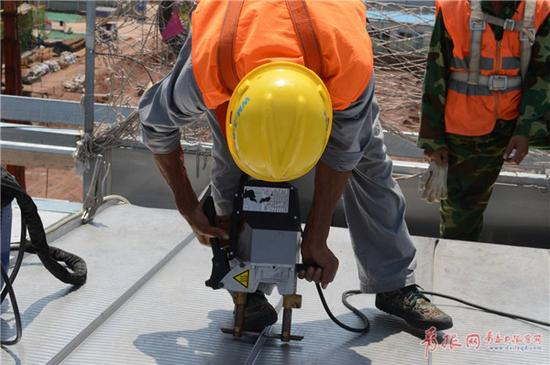 施工人员在焊接不锈钢屋面