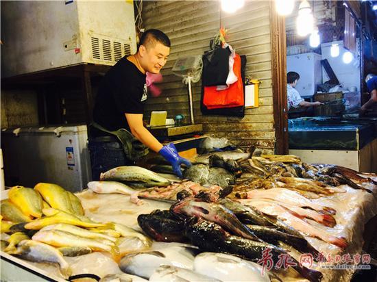 """刚上市的海捕鱼让海鲜摊位""""鲜活""""起来。"""