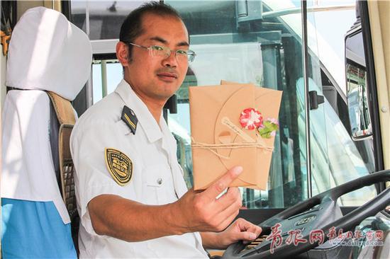 △469路公交车驾驶员唐元贵自制了一批贺卡,乘公交车的学生可以领取贺卡送给老师。