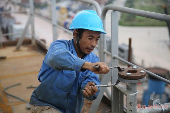 图为一名工人在加固船舶零部件。
