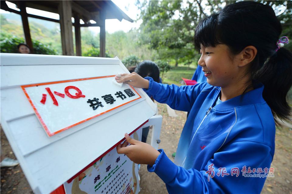 """2017年10月9日,来自青岛市第26中学的徐彤羽对""""小Q共享书屋""""进行擦拭清理。"""
