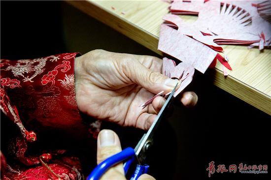 """老人一手握着剪刀,一手反转着红纸,反复之间,一张""""庆十九大,四吉同春""""的剪纸作品便完成了。"""