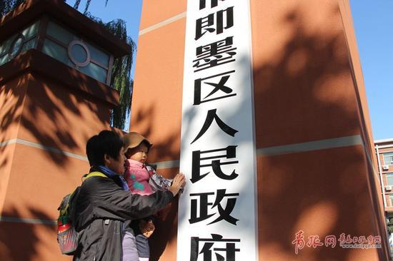 图为市民在青岛市即墨区人民政府门前拍照留念。