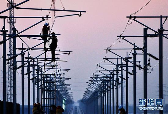 两名中铁电气化局集团的施工人员在济青高铁临淄北至青州区间进行接触网作业。