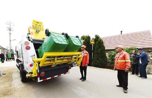 新投入使用的垃圾分类箱和清理车。