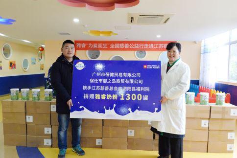 宿迁婴之岛商贸总经理周于钊(左)向泗阳县福利院领导递交捐赠牌