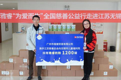 广州市蓓健贸易市场部经理谢昭强向无锡市儿童福利院院长陈国梅递交捐赠牌