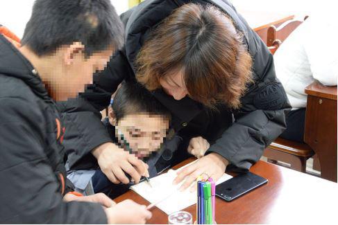 雅睿慈善公益团队成员手把手耐心教导福利院孩子画画
