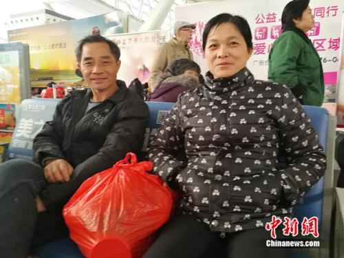 程助华夫妇在广州南站接受记者采访。中新网记者 张尼 摄