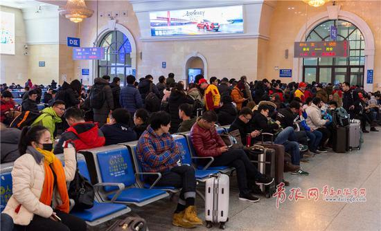 在青岛火车站南候车室,返程旅客等待检票进站。