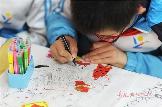 """小学生练习为线板年画上色。(""""青岛观""""摄影师 王海滨)"""