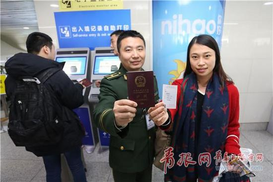 ▲青岛机场边检站民警与旅客一同展示现场打印的出入境记录凭证。解豪 摄