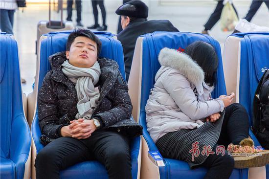 候车旅客在凳子上小憩。