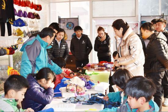 (在王老师的带领下,大家一起参观在学习刺绣技术的光爱孤儿院的孤儿们)