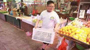 暑假当起小当家 青岛一男孩帮着父母照看水果摊